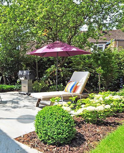 mulch beside lawn chair and umbrella