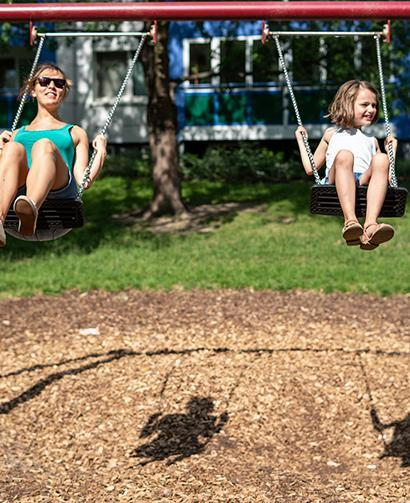 mulch in playground with mom and daughter on swing set